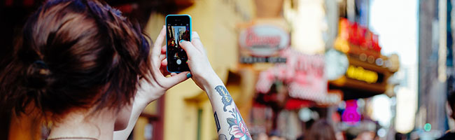 Tattooed person holding up a phone to take a photo of a busy city centre