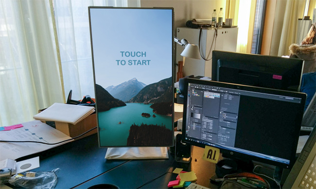 A photo of a monitor with a large vertical surface that says Touch to Start on it