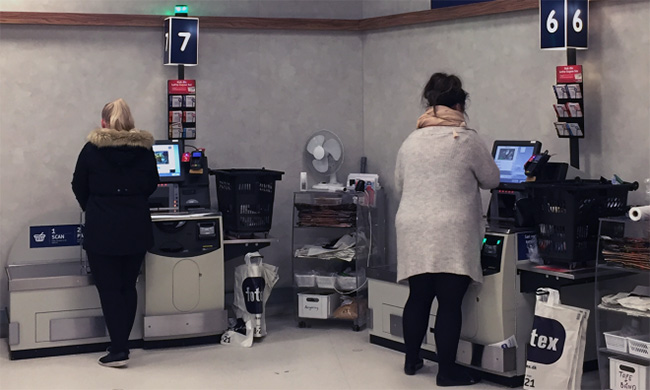 Two women using self-checkout stands at a store