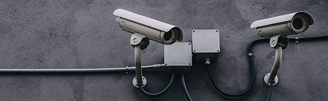 Two CCTV cameras attached to a grey stucco wall