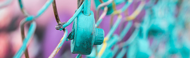 A bright teal combination lock attached to a chain link fence
